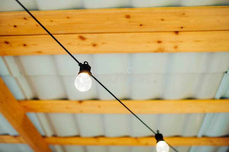 Switched on bulbs with wooden background. Switched on bulbs hanging on a black wire with wooden background royalty free stock images
