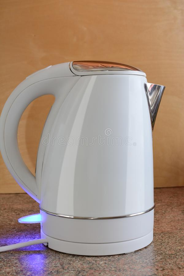 The switched-on electric kettle on a table against the background of a wooden board.  stock photo