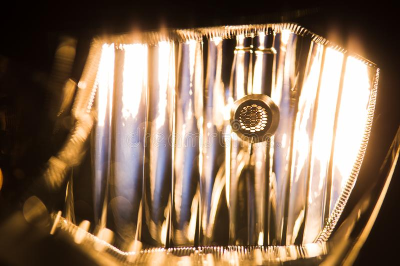 Switched on lamp in headlight closeup. Modern car details royalty free stock images