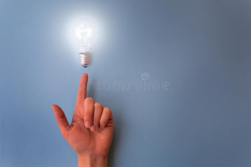 Switched on light bulb on young girl`s hand. Concept of having idea, creatiivity and knowledge royalty free stock image