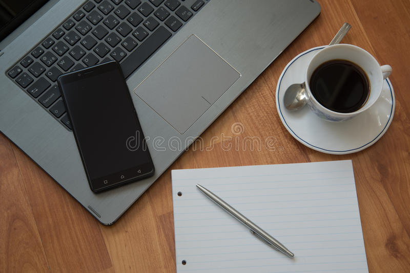 Switched off mobile phone. Nitra, Slovakia - march 28, 2017: Switched off mobile phone screen. Workplace with a laptop, an earphones, notepad, pen and coffee on royalty free stock image