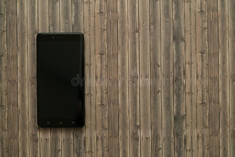 Switched off smartphone. On wooden background royalty free stock photos