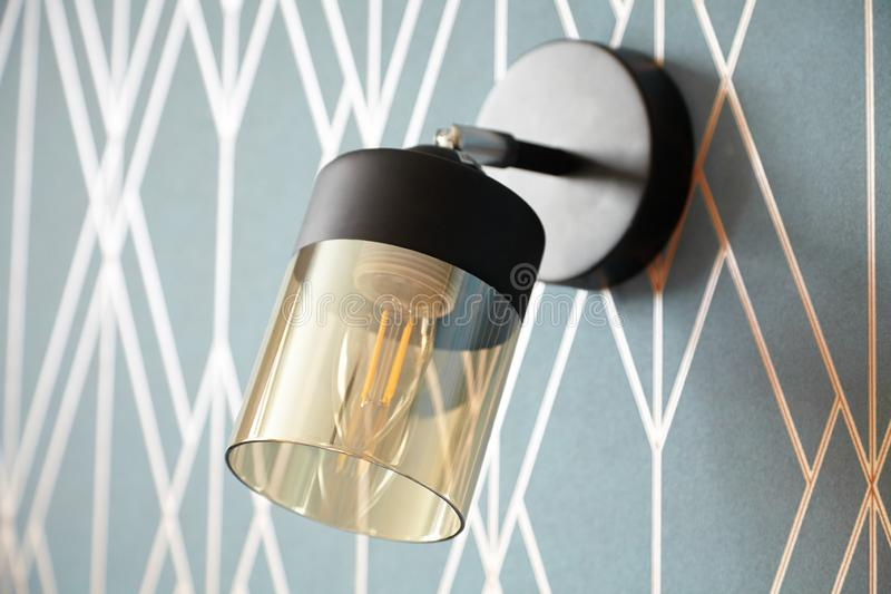 Switched off stylish wall light, bedside lamp on the blue wall close-up. With filament lamp royalty free stock photo