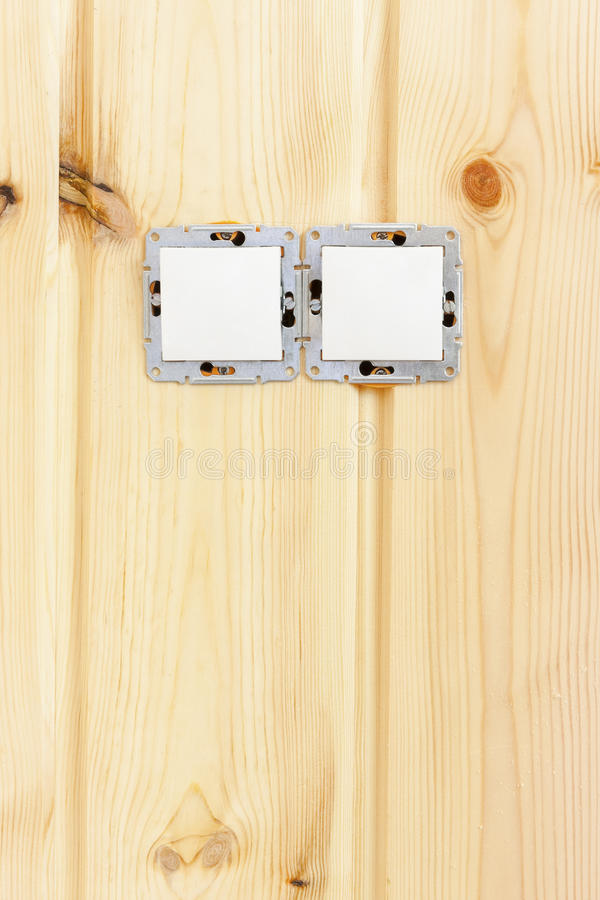 Switches in wooden wall. Concept of unfinished renovation with two white switches without edge covers planted into a nice wooden wall royalty free stock image