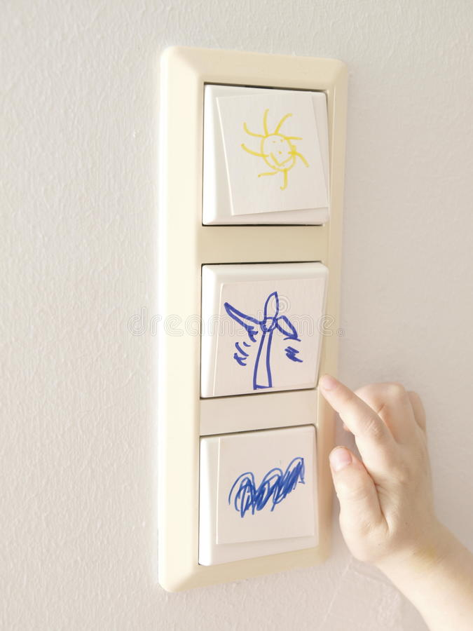 Switching to Alternative Energy. Light switch with alternative energy symbols and a child´s hand royalty free stock photos