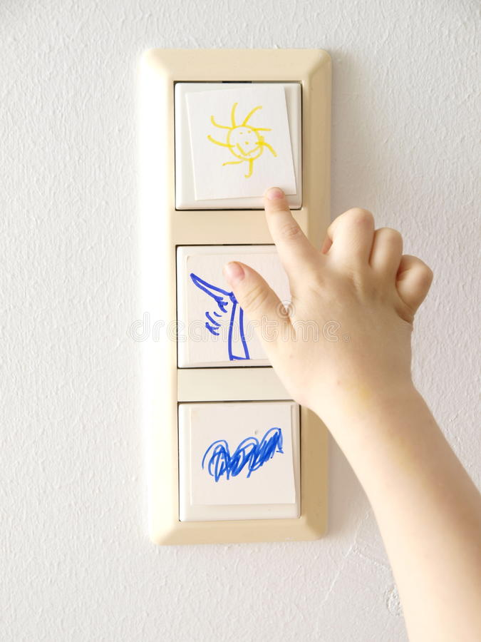 Switching to Alternative Energy. Light switch with alternative energy symbols and a child´s hand royalty free stock images