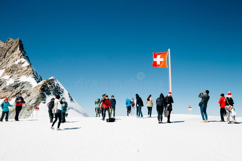 Swiss flag and tourist people on Jungfrau snowy mountain summit in Switzerland. Nature scenery stock image