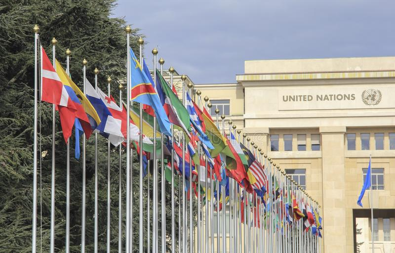 Switzerland; Geneva; March 9, 2018; Two rows of the United Nations member states flags with the United Nations Office in Geneva i. N the background stock image