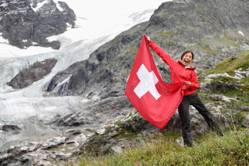 Switzerland hiker cheering showing Swiss flag. Switzerland hiker hiking cheering showing Swiss flag jumping in front of glacier. Happy Asian woman holding big stock image
