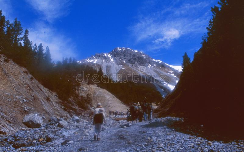 Switzerland: Hikers walking in a dry river bed up to the mountains in the swiss national park royalty free stock photo