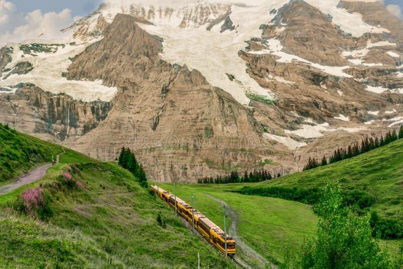 Switzerland , Kandersteg. Yellow train rides on the road in the mountains. stock photo