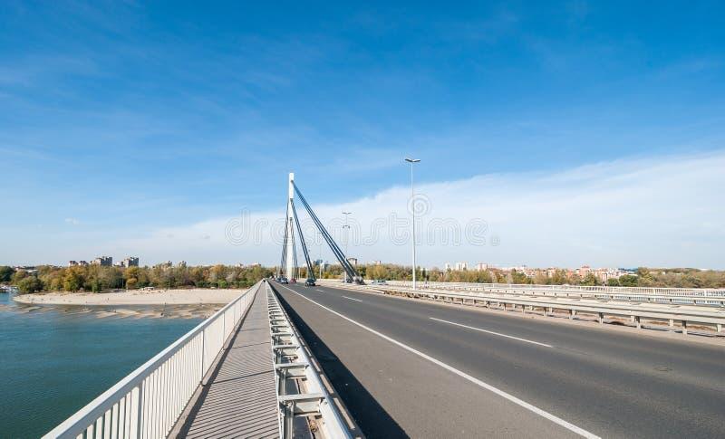 Swoboda most nad Danube rzeką z plażą i budynkiem Novi Sad miasto w Serbia z samochodu jeżdżeniem nad i niebieskim niebem nad obrazy stock
