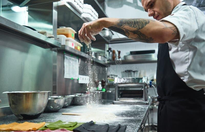 swobodny ruch Przystojny młody szef kuchni nalewa mąkę na kuchennym stole przed robić makaronowi z czerń tatuażami na jego rękach fotografia stock