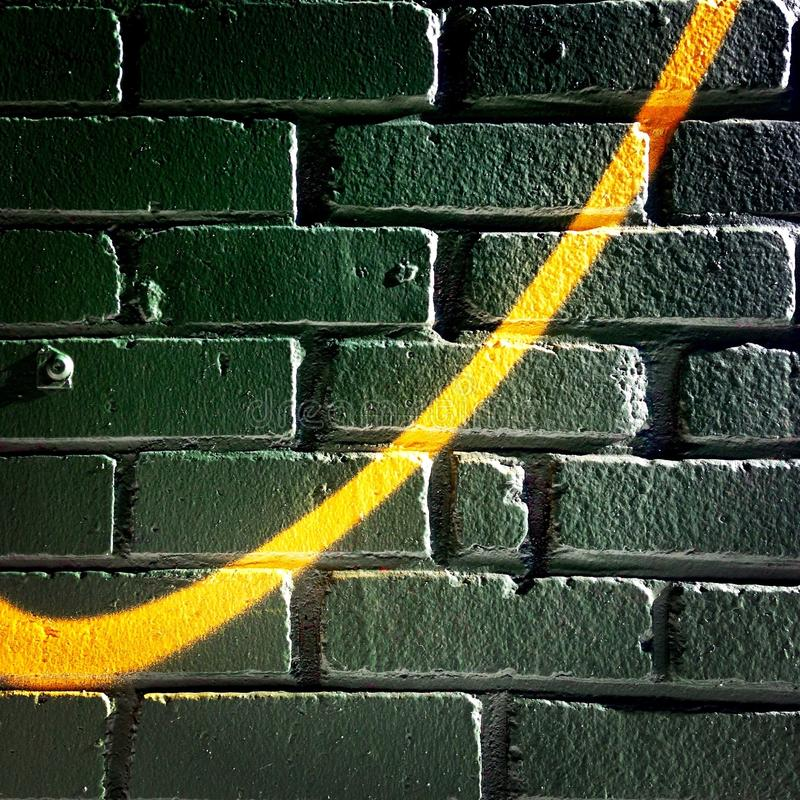 Swoosh on a brick wall. Yellow Swoosh on a green brick wall stock images