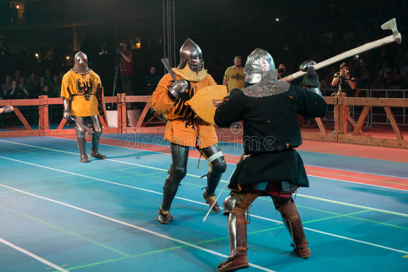 With a sword against a halberd. MOSCOW - DECEMBER 03, 2016: Armored fighters , dressed as knights, fighting at the XI World championship in Medieval combat CUP ` stock image