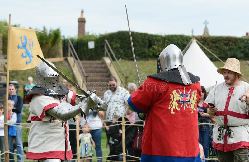Sword fight between two combat fighters dressed in medieval armour stock photos