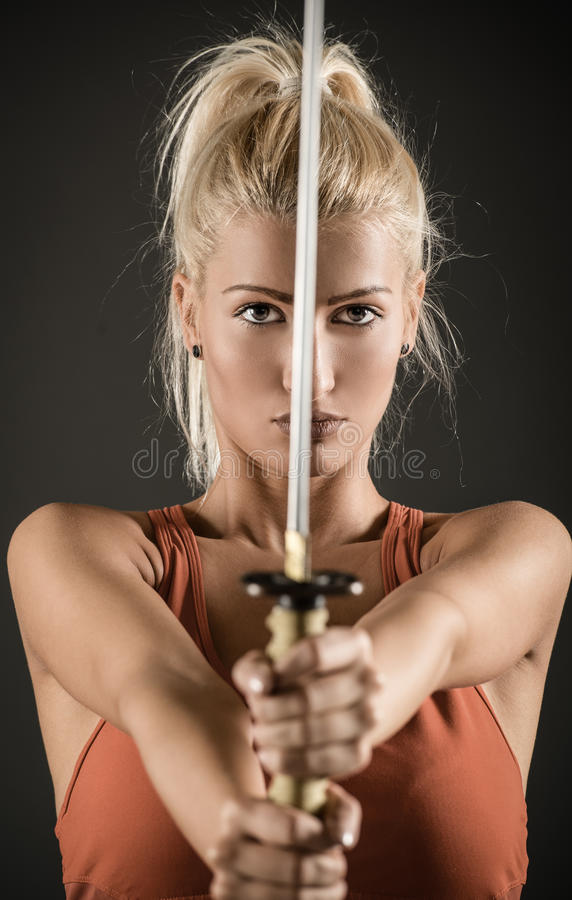 Sword In The Hands Of A Beautiful Woman. Pretty blonde girl with a serious expression on her face holding a katana outstretched hands and looking at the camera stock photos