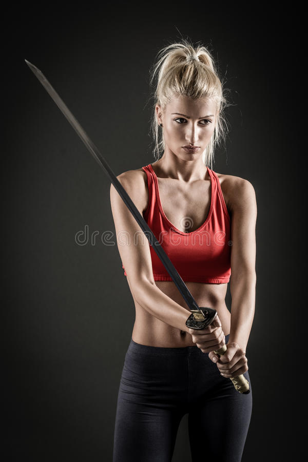Sword In The Hands Of A Beautiful Woman. Pretty girl with a serious expression on her face holding a katana stock photography