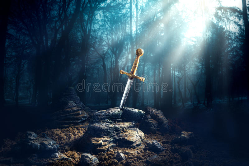 Sword in the stone excalibur. High contrast image of Excalibur, sword in the stone with light rays and dust specs in a dark forest