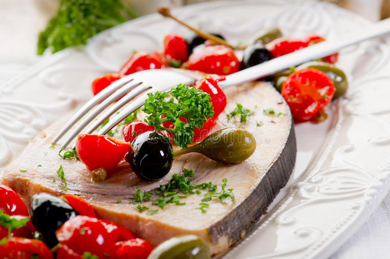 Swordfish with tomatoes capers royalty free stock photography
