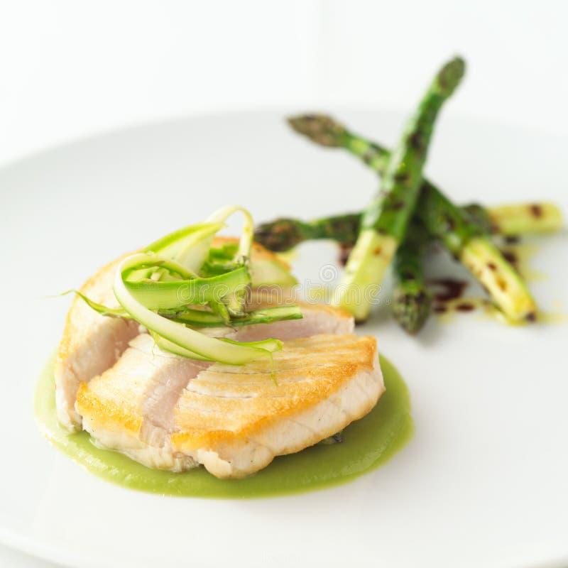Swordfish z asparagusa i zieleni chickpeas na białym tle zdjęcie royalty free