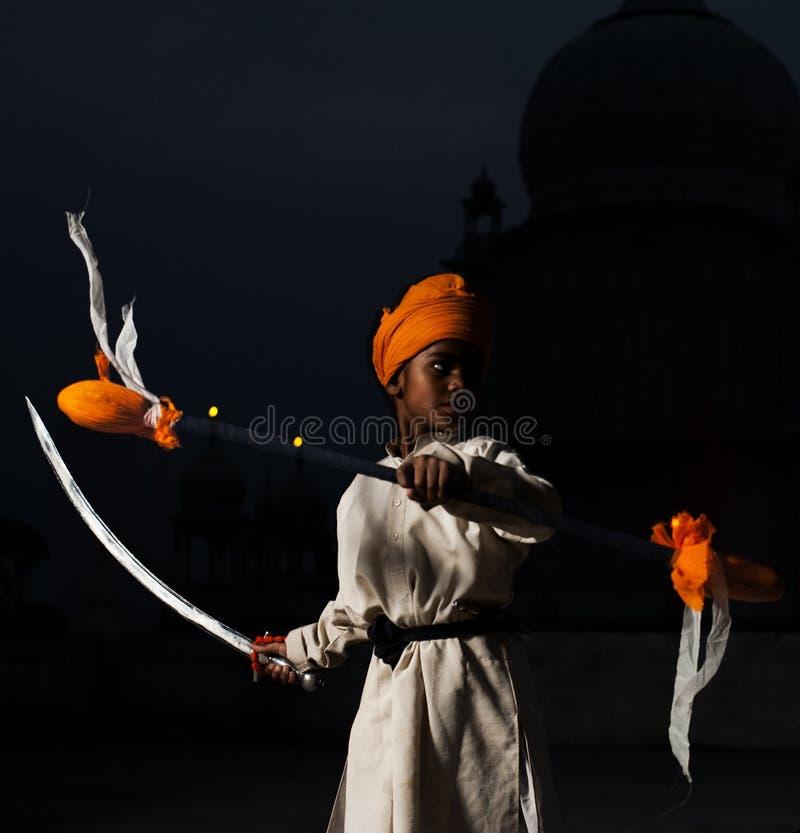 Swordplay sikh di pratica di colore giallo del ragazzo fotografie stock