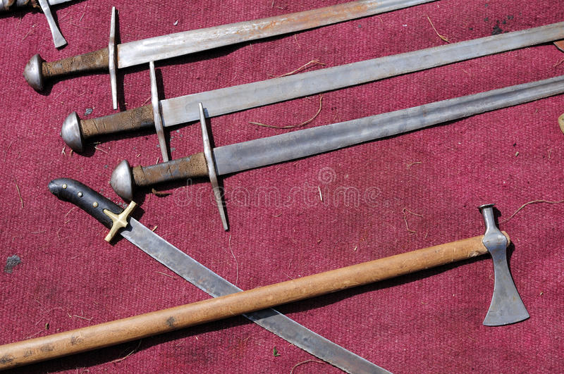 Swords and battle-axes. On red material stock images