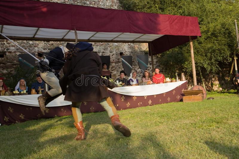 Swordsmen performing and fighting in front of lords and ladies at a banquet. Medieval reenactment with two noble swordsmen dueling in front of lords and ladies royalty free stock image