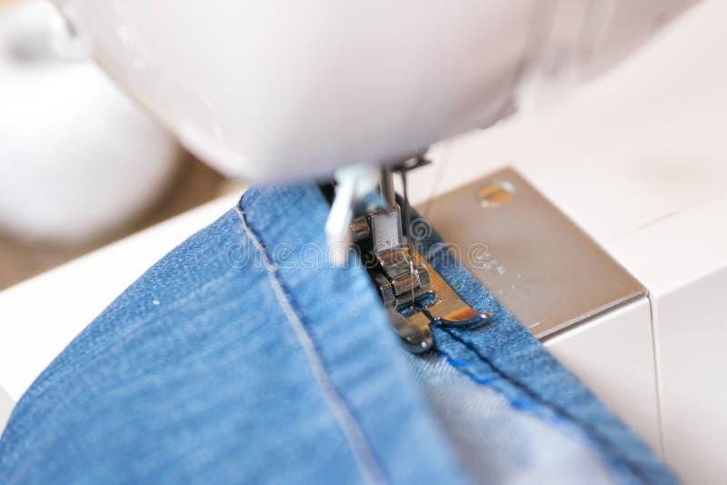 Sy grov bomullstvilljeans med symaskinen Reparationsjeans vid symaskinen royaltyfria bilder
