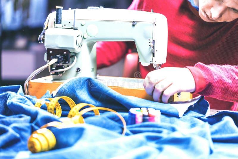 Sy grov bomullstvilljeans med symaskinen Reparationsjeans vid symaskinen Förändringsjeans som fållar ett par jeans som är handgjo royaltyfri bild