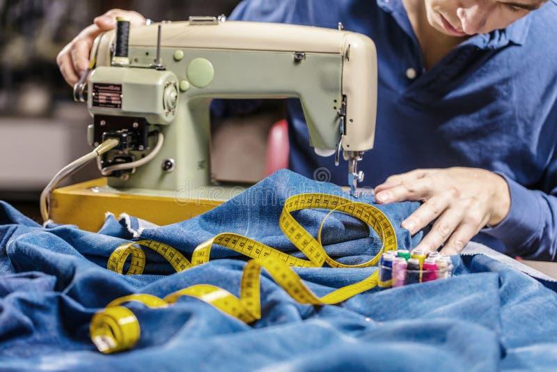 Sy grov bomullstvilljeans med symaskinen Reparationsjeans vid symaskinen Förändringsjeans som fållar ett par jeans som är handgjo arkivfoton