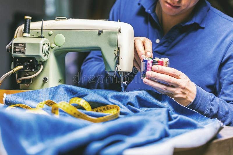 Sy grov bomullstvilljeans med symaskinen Reparationsjeans vid symaskinen Förändringsjeans som fållar ett par jeans som är handgjo arkivbilder