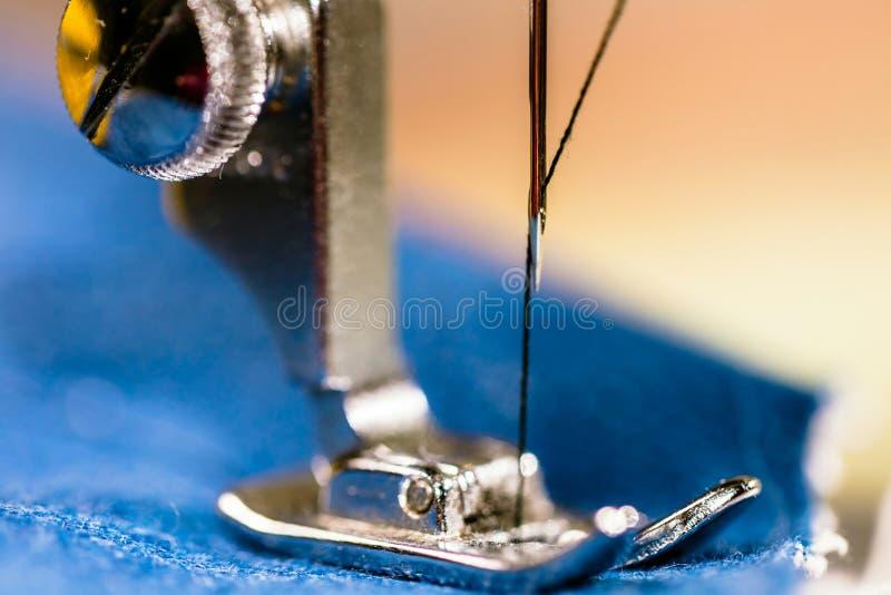 Sy grov bomullstvilljeans med symaskinen Reparationsjeans vid symaskinen Förändringsjeans som fållar ett par jeans som är handgjo royaltyfri fotografi