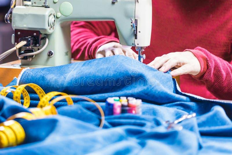 Sy grov bomullstvilljeans med symaskinen Reparationsjeans vid symaskinen Förändringsjeans som fållar ett par jeans som är handgjo arkivbild