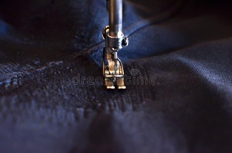 Sy, häftklammer ett hål i mörk jeans eller att sticka sweatpants med en symaskin Del av symaskin- och grov bomullstvillcloseupen arkivbild
