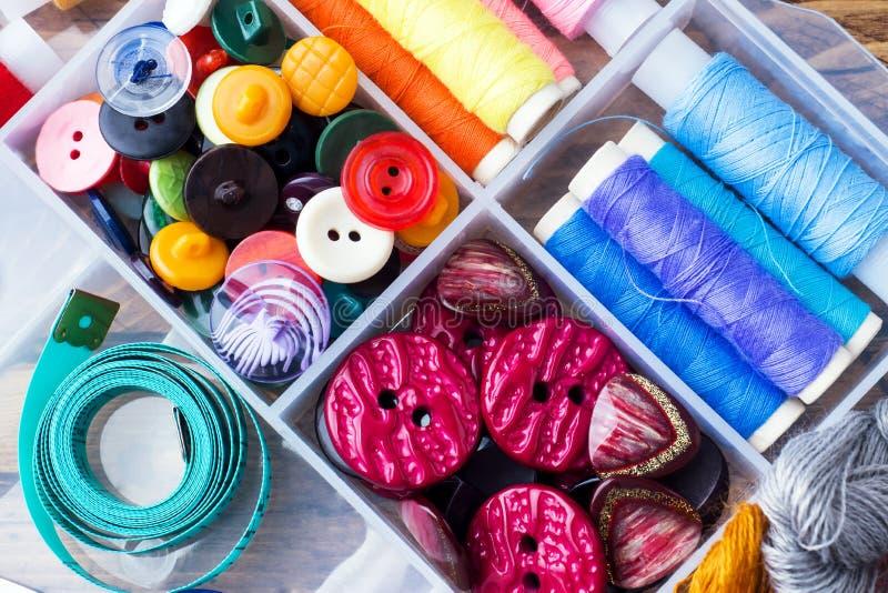 Sy hjälpmedlet för handarbete färgade trådar, cm och knappar med ett par av sax på tabellen Närbild arkivbild