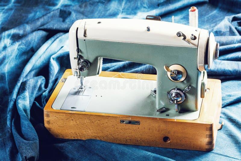 Sy indigoblå grov bomullstvilljeans med symaskinen, industriellt begrepp för plagg arkivfoto