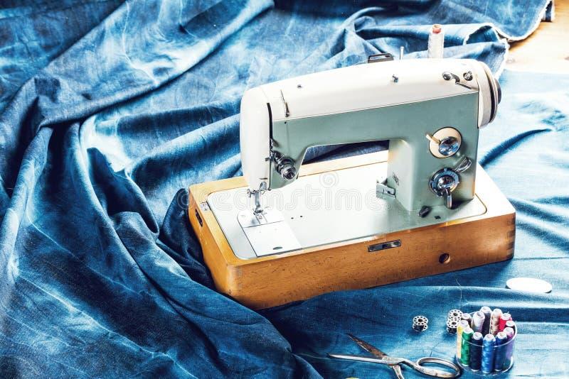 Sy indigoblå grov bomullstvilljeans med symaskinen, industriellt begrepp för plagg royaltyfri fotografi