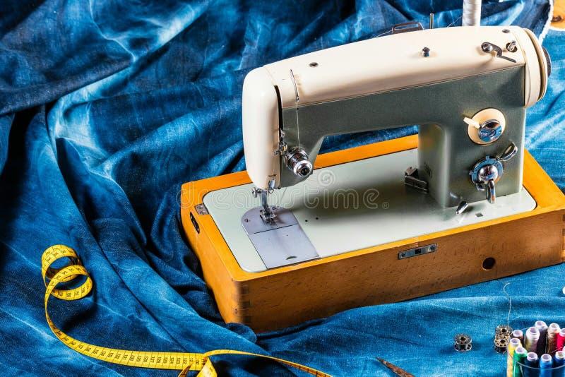 Sy indigoblå grov bomullstvilljeans med symaskinen, industriellt begrepp för plagg arkivbilder