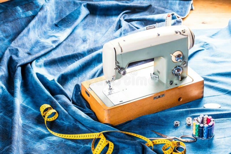 Sy indigoblå grov bomullstvilljeans med symaskinen, industriellt begrepp för plagg royaltyfri bild