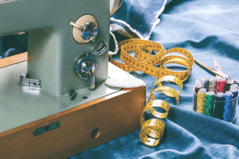 Sy indigoblå grov bomullstvilljeans med symaskinen, industriellt begrepp för plagg arkivbild