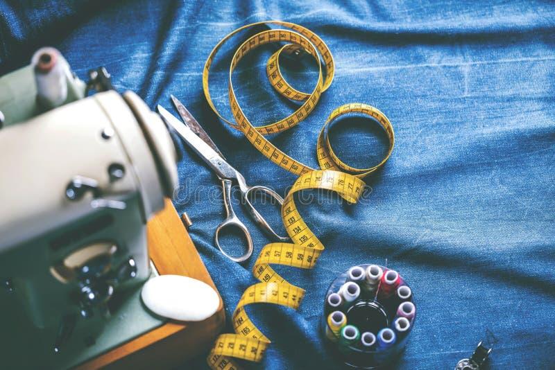 Sy indigoblå grov bomullstvilljeans med symaskinen, industriellt begrepp för plagg royaltyfria bilder