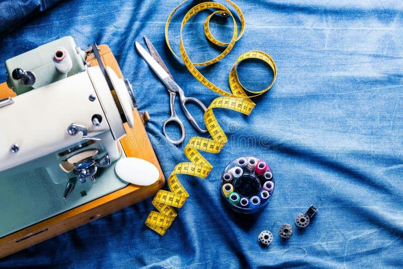 Sy indigoblå grov bomullstvilljeans med symaskinen, industriellt begrepp för plagg arkivfoton
