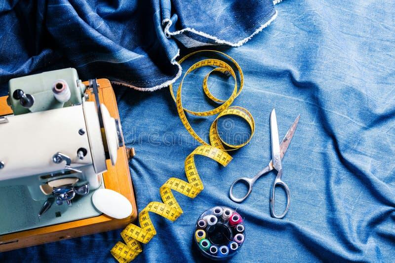 Sy indigoblå grov bomullstvilljeans med symaskinen, industriellt begrepp för plagg royaltyfria foton