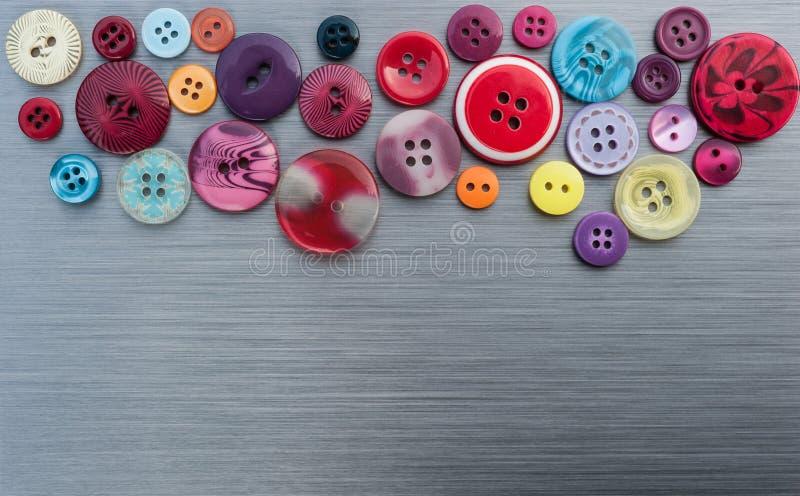 Sy knappar på borstad metallbakgrund fotografering för bildbyråer