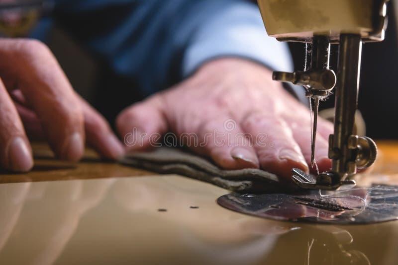Sy processen av läderbältet gamal mans händer bak att sy Läderseminarium sy för textiltappning som är industriellt royaltyfri bild