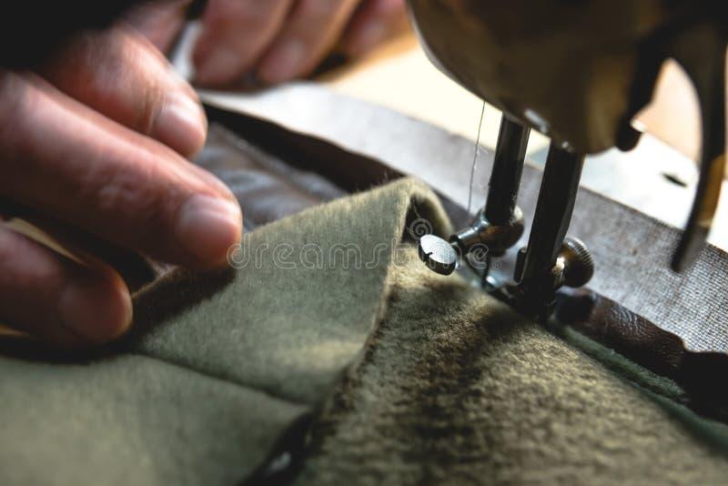 Sy processen av läderbältet gamal mans händer bak att sy Läderseminarium sy för textiltappning som är industriellt arkivbilder