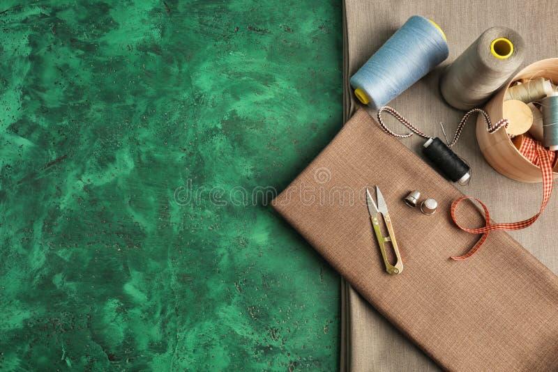 Sy tillbehör med tyg på färg texturerad bakgrund arkivbild