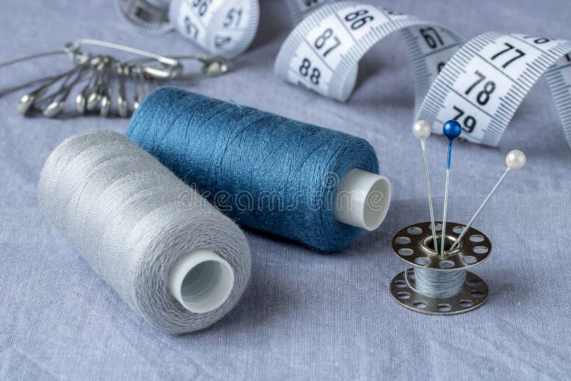 Sy tillbehör och tillbehör för handarbete i grå färg-blått skuggor arkivfoto
