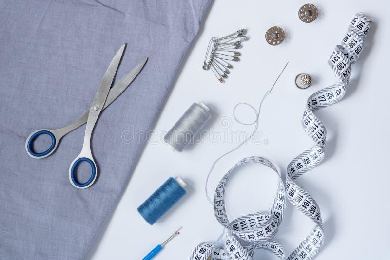 Sy tillbehör och tillbehör för handarbete i grå färg-blått skuggor royaltyfria bilder